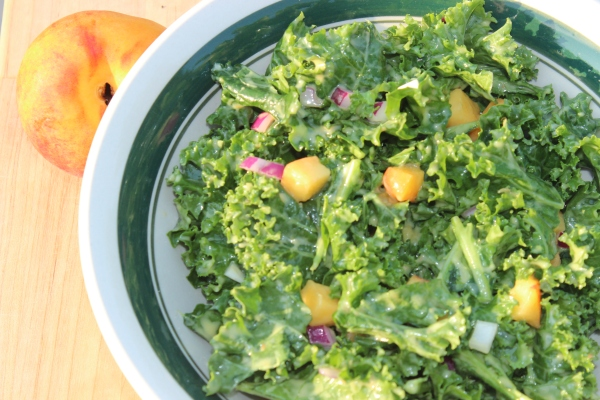 This beautiful peachy kale salad will be a hit at your dinner table or a potluck!