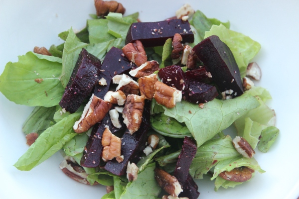 Simple salad of sliced beets, chopped pecans, and field greens